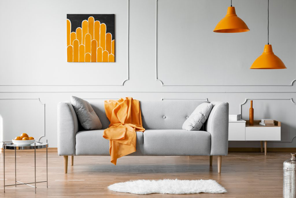 Orange blanket on grey couch in living room with orange lamps and art.